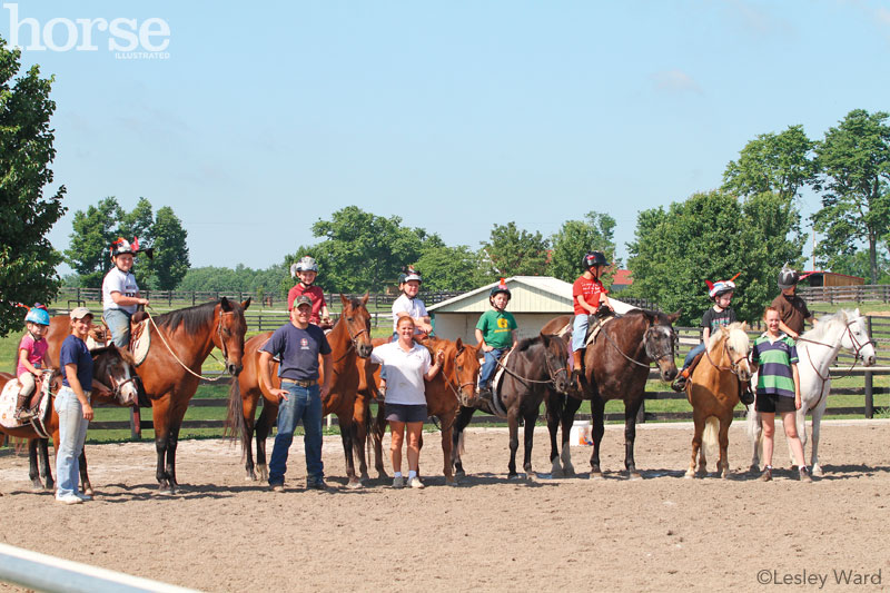 Group of campers, horses, and instructors at a summer horse camp