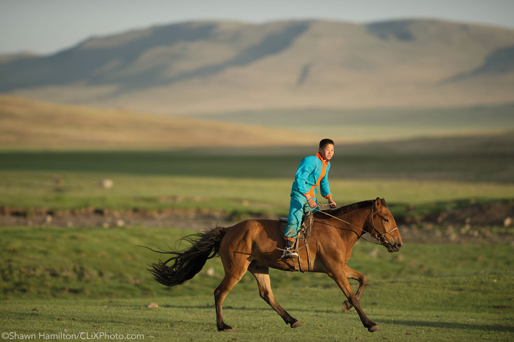 Young boy riding a horse in Mongolia