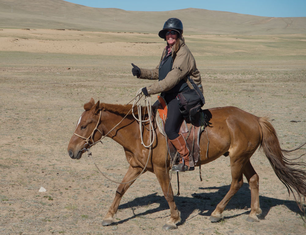 Photographer Shawn Hamilton riding a horse in Mongolia