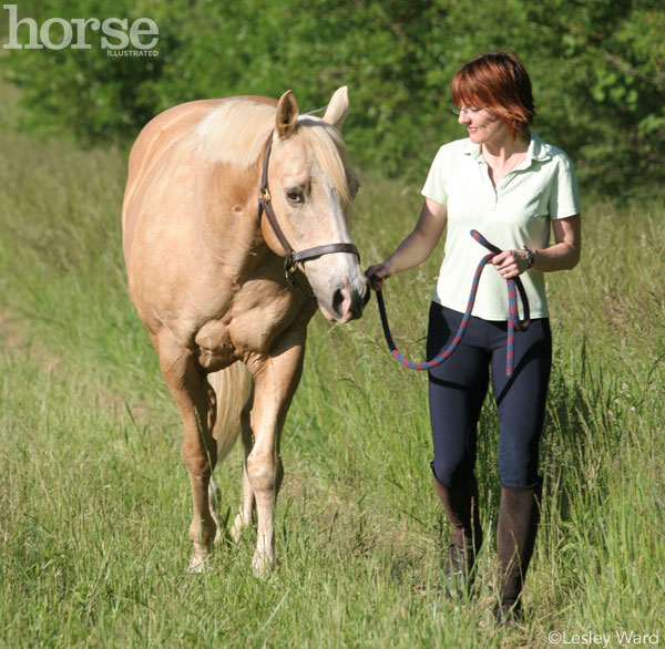 Woman leading a palomino horse through a grassy field