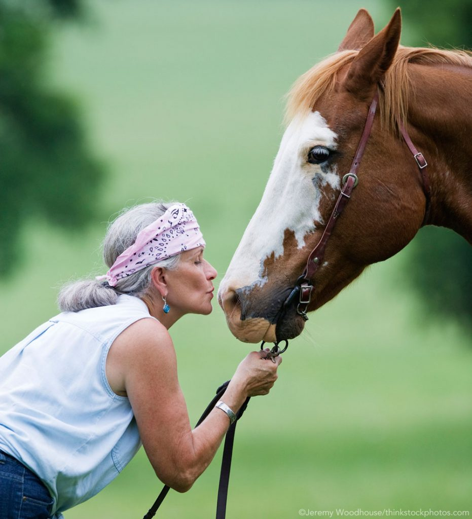 Older Woman kissing a Paint horse - Riding into the Golden Years