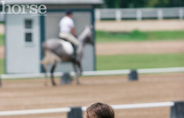 Spectator and dog watching a horse show