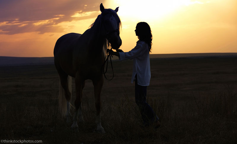 Woman and horse at sunset