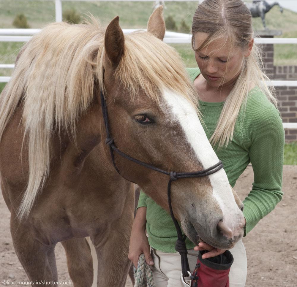 Woman feeding treats to her horse