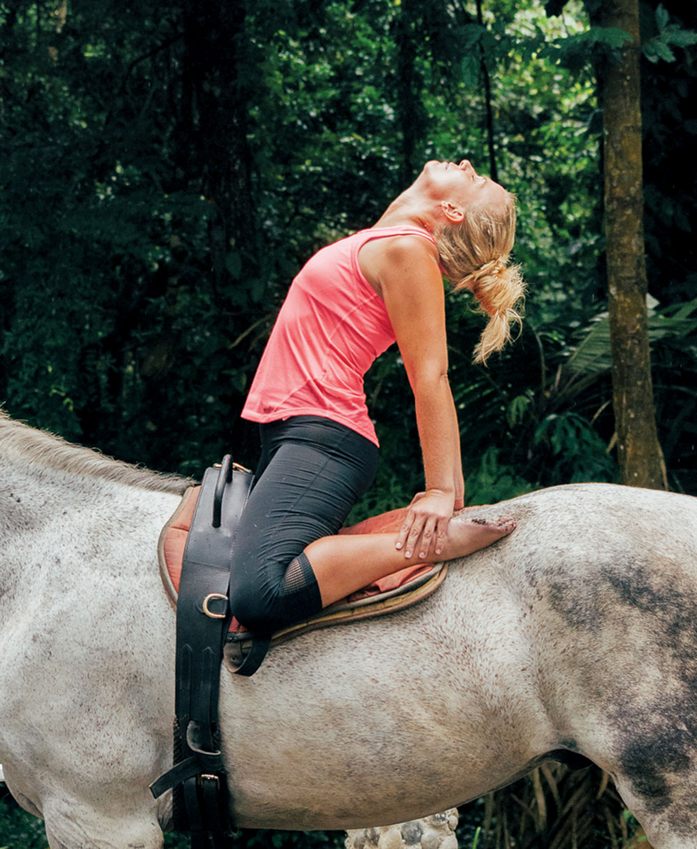 A rider practicing yoga on horseback at Kindred Spirits
