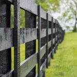 Black four-board post-and-board fence