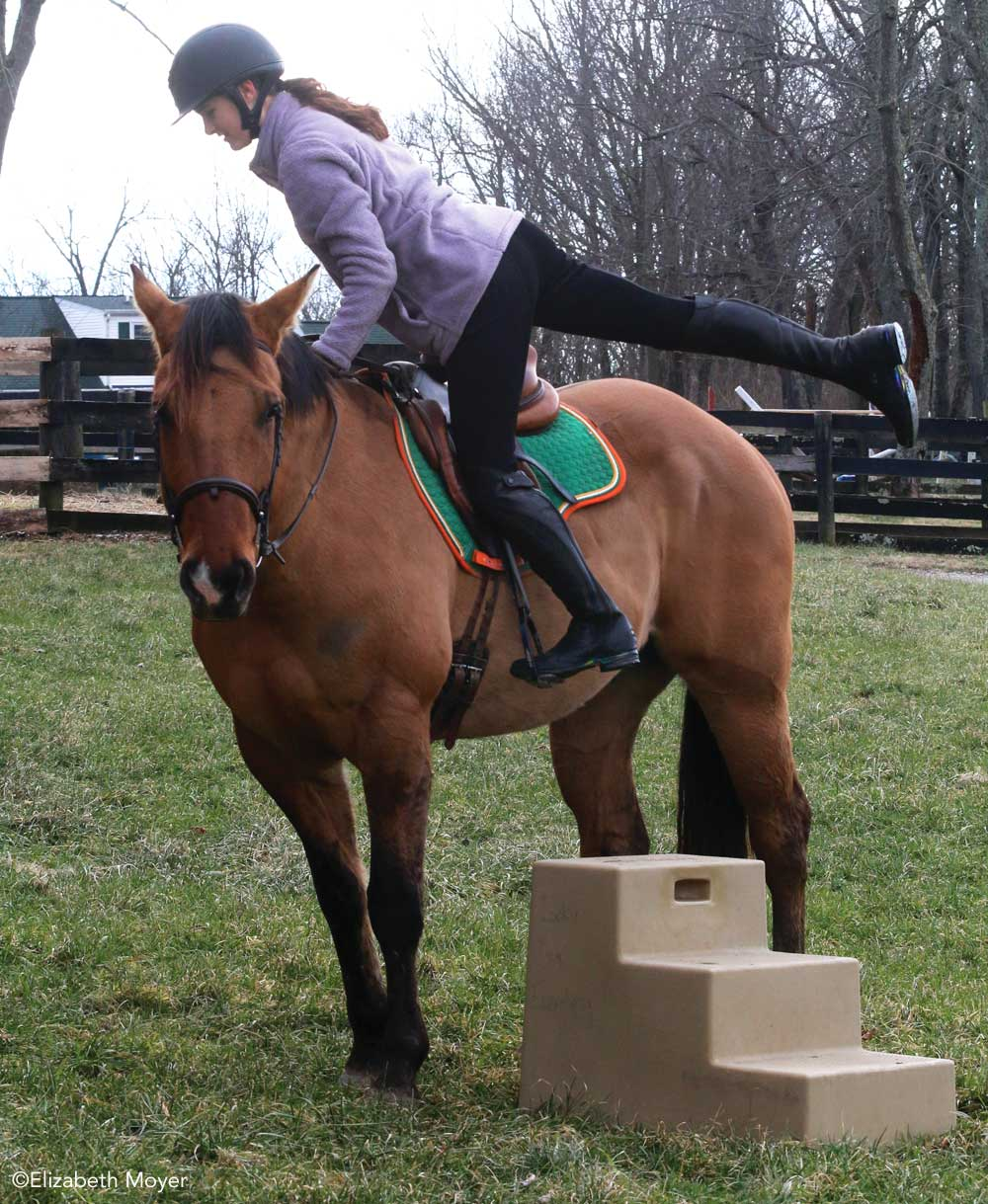Rider mounting a horse from a mounting block