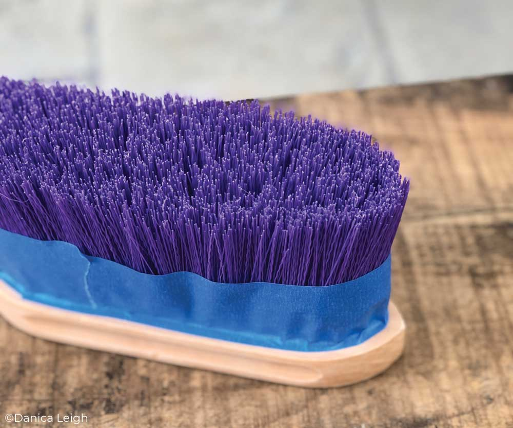 A horse brush with blue painters tape around the bristles.