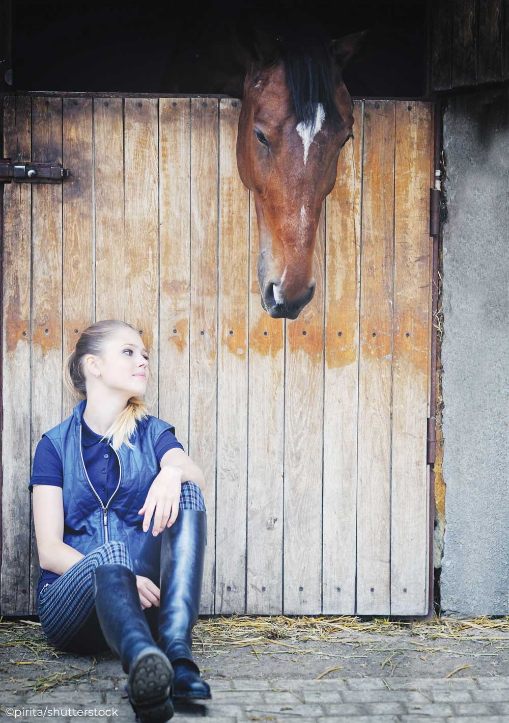 Girl sitting outside a horse's stall