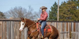 Trainer Heather Young riding a Paint Horse at the lope.