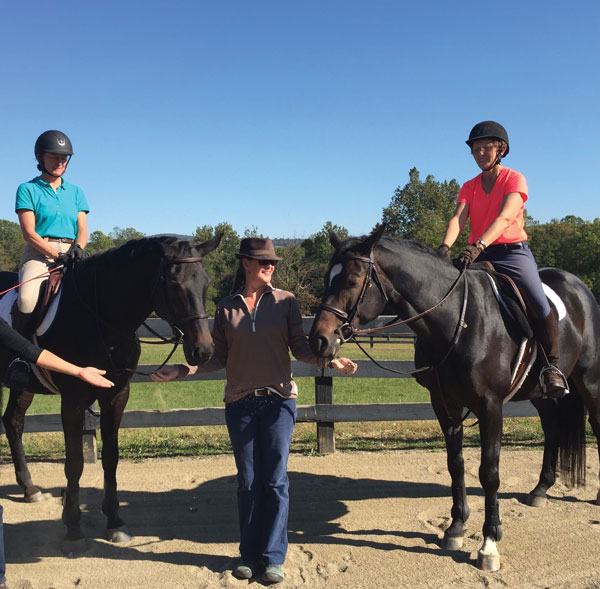 Riders with animal communicator standing between two horses.