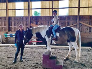 Horse and rider in arena with trainer.
