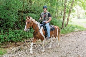 Horse rider with mounted orienteering gear.
