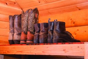 Boots on a shelf in clean tack room.