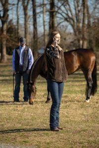 Woman calling virtual veterinarian while standing near horse.