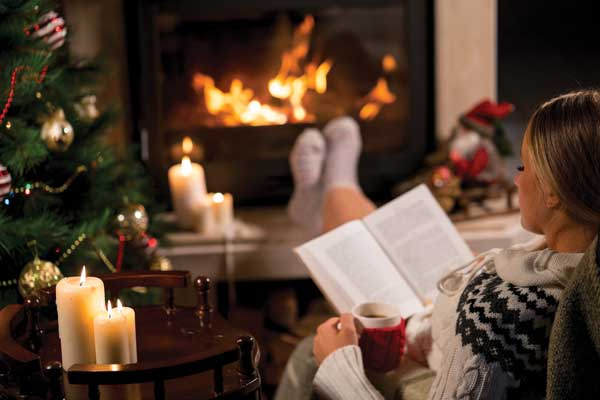 Reading book by the fire and Christmas tree
