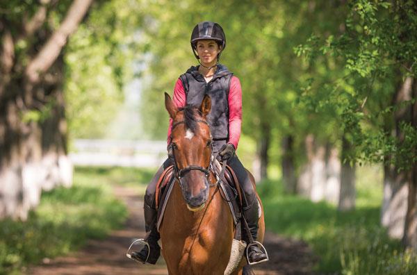 Woman horseback riding solo on trail.