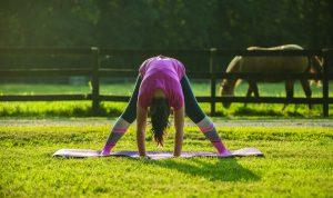 Person practicing yoga forward fold.